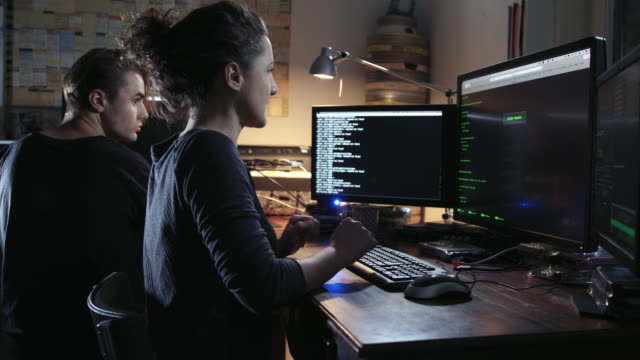 Digital threat - nerdy female computer hacker and a male computer geek typing computer code in computer language while trying to break into a secured computer network during night - she leaves the frame in the end.