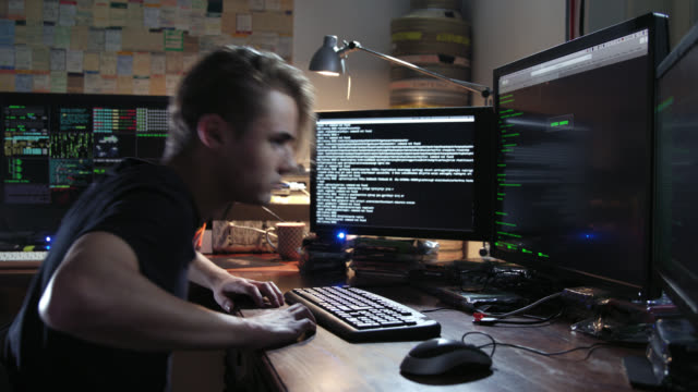Digital threat - nerdy young male computer hacker geek typing computer code in computer language while trying to break into a secured computer network during nigh – close shot – he leaves the frame in the end.