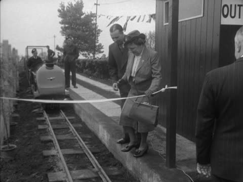 A dignitary cuts the tape at the opening of the minature railway at Alexandra Park in London