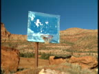 Dilapidated outdoor basketball hoop w/ discolored light blue backboard red green grass field BG Mohave County Arizona Strip AZ