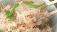 A diner removes a portion of crab bowl rice with chopsticks.