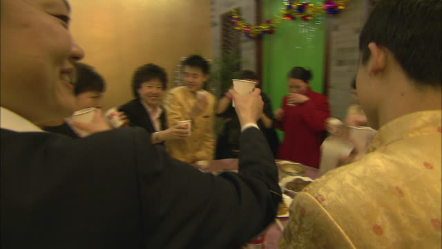 Diners at a round table stand to drink a toast in decorated paper cups for Chinese New Year.
