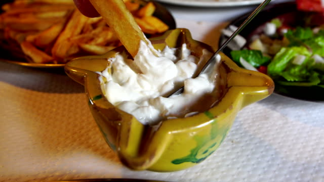 Dipping french fry in alioli - typical bowl