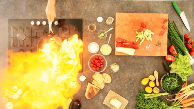 Draufsicht Foto von einem Mann Kochen mit Feuer im der Küche
