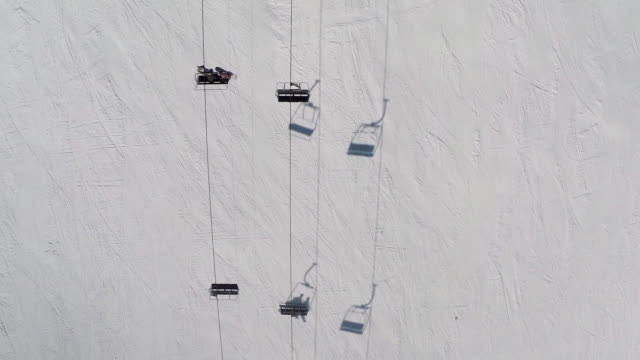 Directly above shot of ski lift passing over snow covered mountain