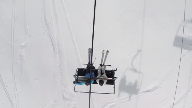 Directly above shot of skiers riding ski lift passing over snow covered mountain