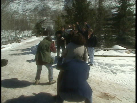 WS Director John Landis taking pictures while cast of Animal House throw snowballs at him and some behind the scenes people standing nearby