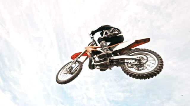 SLO MO Dirt biker jumping over dirt ramp