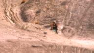 WS TD PAN Dirt biker riding along barren hillside and jumping / Salton City, California, USA