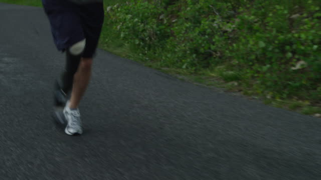 MS TS TU Disabled athlete with artificial limb jogging on rural road / American Fork Canyon, Utah, USA