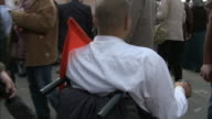 TS Disabled spectator in motorized wheelchair holding Egyptian flag riding through crowd in Tahrir Square / Cairo Egypt