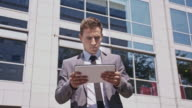 Disappointed businessman using digital tablet