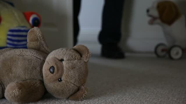 Discarded Teddy bear, child's room, man walks in.