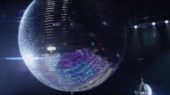 CU disco ball spinning above nightclub dance floor and bar