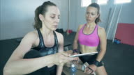 Discussion with the personal trainer at the gym using digital tablet.