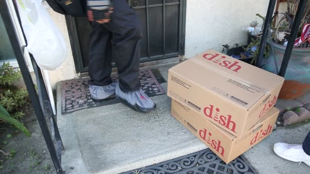 A Dish Network technician carries boxes of Dish equipment into a customer's home before performing an installation upgrade at a suburban home in...