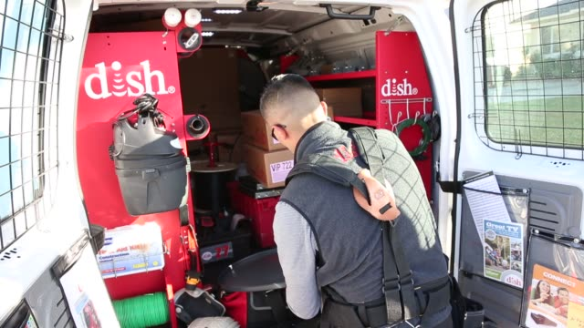 A Dish Network technician sorts through equipment and parts before performing an installation upgrade for a customer at their suburban home in Downey...