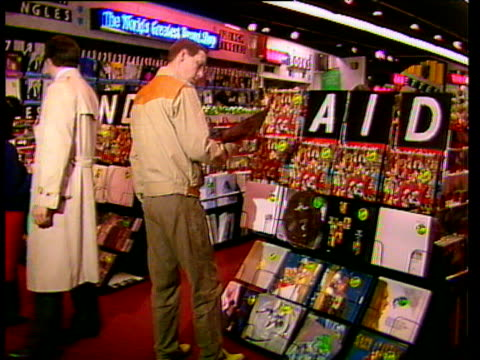 Display of various records on rack in shop with sequence of cards across top of rack spelling out