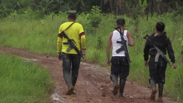 Dissident guerrillas patrol the banks of the Inirida river rifles slung over their shoulders
