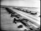 Distant view of graduating class of aerial gunners / aerial view of row B17 bombers parked down a runway with crews lined up in front of each / class...