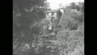 Distant Villa Lou Viei seen through trees / upper room and roof / people probably journalists stand at end of gravel road with a semicircular gate /...