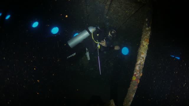 Diver swimming through boat cabin of Boga Shipwreck, Bali, Indonesia