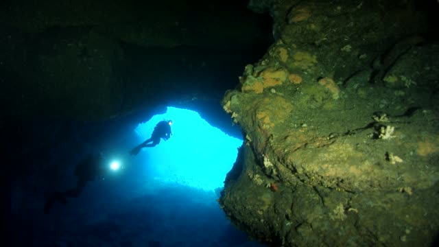 Divers inside a cave with light in Pianosa Island
