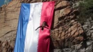 Divers jumps from Acapulcos La Quebrada cliff adorned with the French flag in solidarity for the victims of the Paris attacks