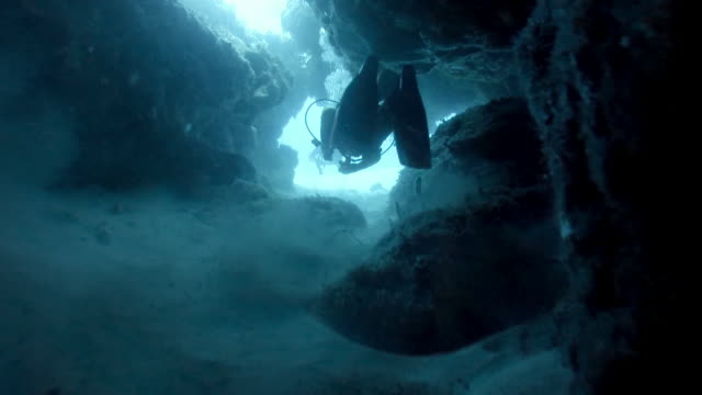 WS Divers swimming through cave in coral reef