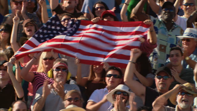HA WS PAN Diverse crowd cheering and holding American flag in bleachers / Homestead, FL, USA