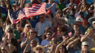 HA WS PAN Diverse crowd standing up and waving American flags in bleachers / Homestead, FL, USA