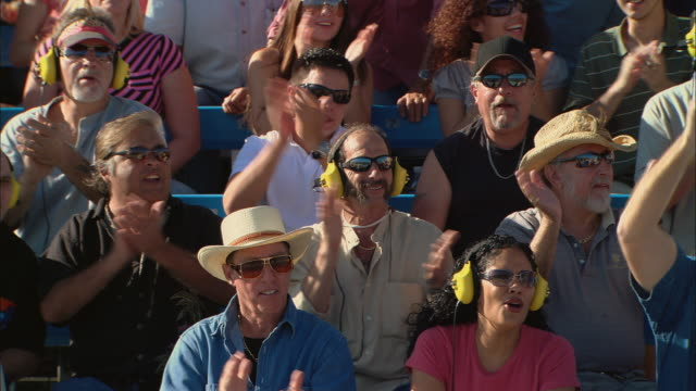 HA MS Diverse crowd wearing ear protectors and watching, then jumps up and cheers in bleachers / Homestead, FL, USA