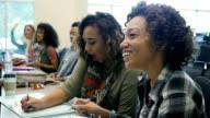 Diverse female college students take notes during lecture
