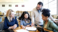 Diverse group of adult college students studying together in library during tutoring session