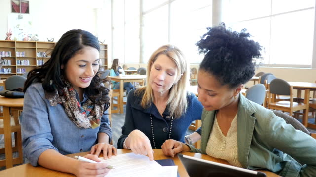 Diverse group of adult women studying together in college library for class assignment