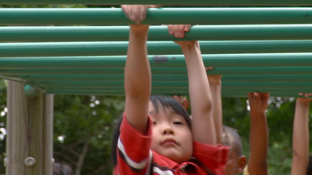 MS Diverse group of children swinging on monkey bars on playground/ Richmond, Virginia