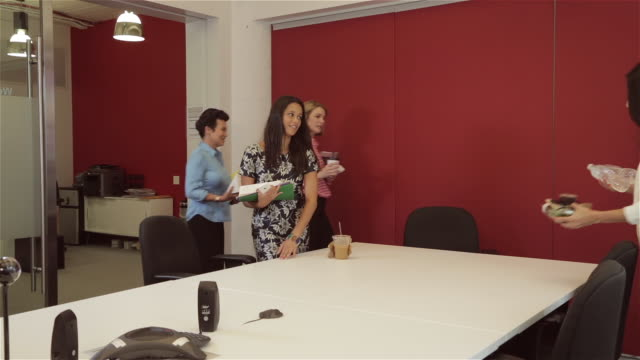 Diverse group of female executives walk into board room for lunch meeting