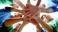Heterogene Gruppe von Junior High School Fußballspieler mit Hände in ein Wirrwarr
