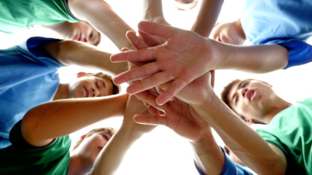 Diverse group of junior high school soccer players with hands in a huddle