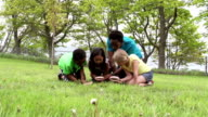 Diverse group of kids kneeling in grass with magnifying glass