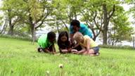 Gruppo eterogeneo di ragazzi in ginocchio in erba con la lente d'ingrandimento