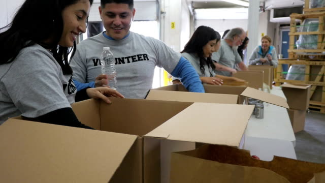 Diverse group of volunteers sorting donations into boxes at food bank