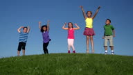 Diverse kids jumping on a hill in slow motion