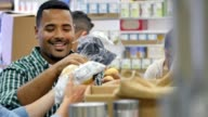 Diverse male friends talk with one another while volunteering in food bank