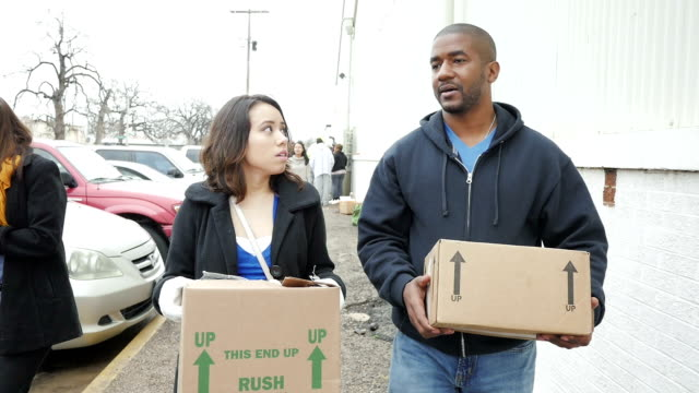 Diverse man and woman carrying boxes of donated food after waiting in line at food bank on cold day