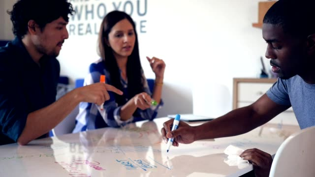 Diverse millennial creative professionals use whiteboard table while brainstorming ideas
