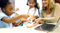 Diverse private STEM elementary schoolgirls are excited as they build a robot