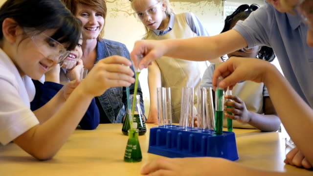 Diverse students in private elementary school science chemistry classroom conducting experiment