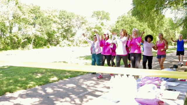 Diverse team crossing finish line during breast cancer awareness charity race