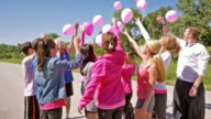 Diverse team of people releasing pink balloons at breast cancer awareness charity race